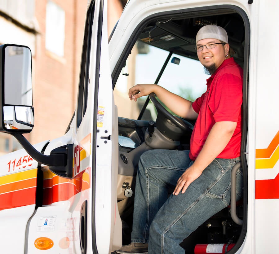Man with red shirt sitting in an RTS truck cab with the door open smiling