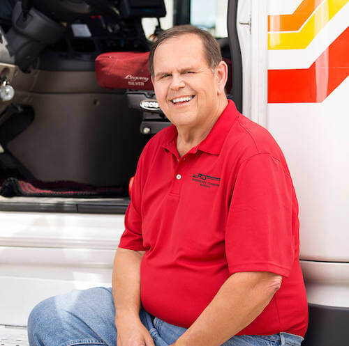 RTS truck driver with red shirt smiling sitting in front of the open door of a truck cab